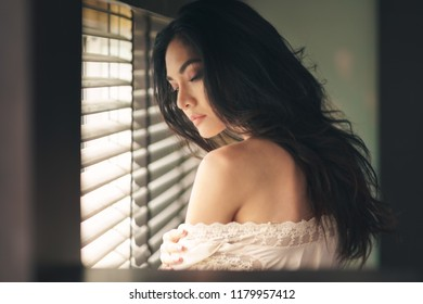 Portrait of sexy young woman in white dress sitting near jalousie