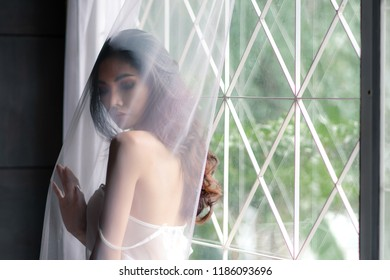 Portrait of sexy young woman in white dress posing under curtain