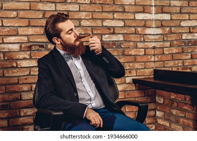 Portrait of a sharming brutal amazing man sitting on a chair and setting fire to a cigar against the background of a brick wall. Cigar concept