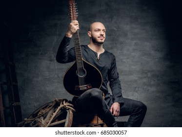 Portrait of a shaved head male musician dressed in old Celtic clothes sits on a wooden box and performing old mandolin.