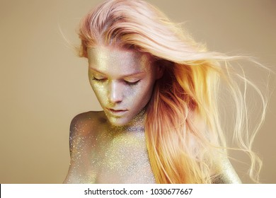 Portrait of Shining Beautiful Woman with Sparkles on her Face and body. Girl with Art Make-Up in Color Light. flying pink hair Model with Colorful Makeup