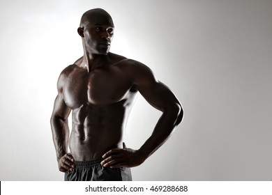 Portrait of shirtless male model posing against grey background. African young man with muscular body standing with hands on hips and looking away.