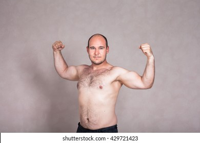 Portrait of shirtless man posing and showing his strong arms and hairy body.