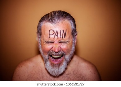 Portrait of a shirtless man with the word pain on the forehead