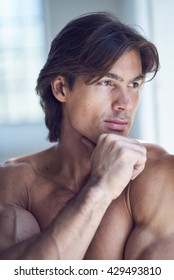 Portrait of shirtless muscular male in natural light.