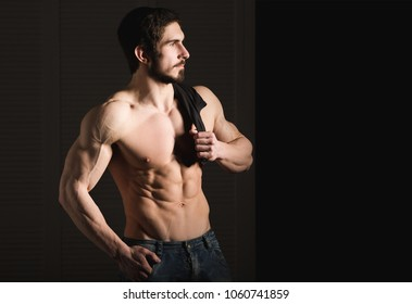 Portrait of shirtless muscular man in a jeans. Young male hunk showing his perfect body and muscles on black background.