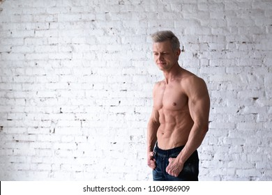 Portrait of shirtless muscular man in a jeans. Young male hunk showing his perfect body and muscles on white brick background.