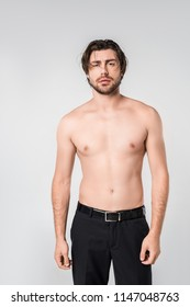 portrait of shirtless pensive man in black pants on grey background