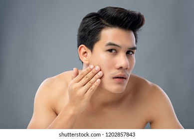 Portrait of shirtless young handsome Asian man checking his face for skin care and beauty concepts, studio shot isolated on gray background
