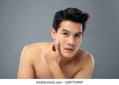 Portrait of shirtless young handsome Asian man touching and checking his face for skin care and beauty concepts studio shot