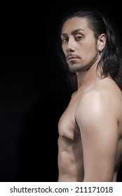 Portrait Of Shirtless Young Man Over Black Background