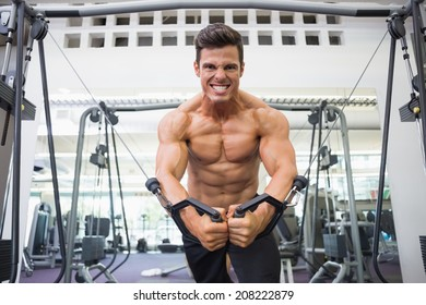 Portrait of a shirtless young muscular man using resistance band in gym