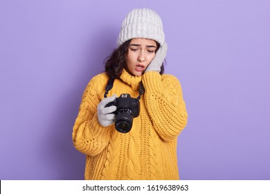 Portrait of shocked attractive emotional brunette holding photocamera in one hand, looking through photos, unsatisfied with results, being disappointed with quality. People and emotions concept.