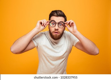 Portrait of a shocked bearded man in eyeglasses looking at camera isolated over yellow background