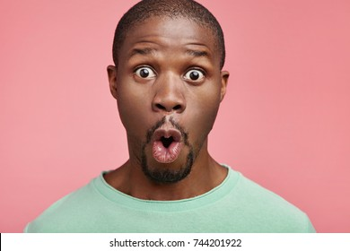Portrait of shocked black male says wow, looks bugged eyes and rounded mouth, being amazed to see something unexpected. Terrified Afro American guy with surpised expression. Emotions concept