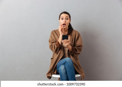 Portrait of a shocked casual asian woman holding mobile phone while sitting on a chair over gray background