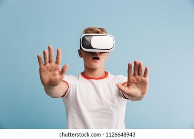 Portrait of a shocked casual teenage boy wearing 3D virtual reality headset isolated over blue background