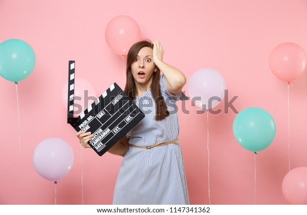 Portrait of shocked concerned woman with opened mouth in blue dress clinging to head holding classic black film making clapperboard on pink background with colorful air baloon. Birthday holiday party