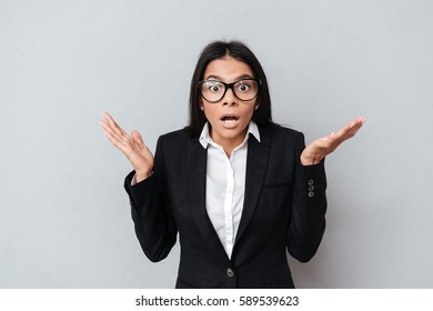 Portrait of a shocked confused business woman in eyeglasses gesturing with hands over gray background