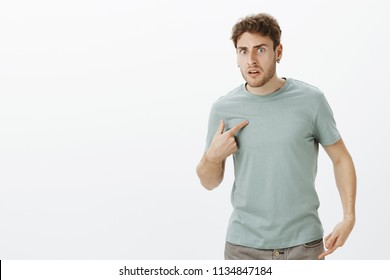 Portrait of shocked frustrated handsome european man in earrings, pointing at himself with index finger and frowning, asking question, being displeased with terrible offencive words over gray wall