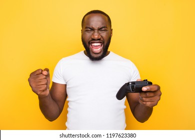 Portrait of shocked funny funky crazy excited delighted man, playing, winning online game, opened mouth, isolated over bright vivid yellow background