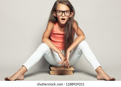 Portrait of a shocked funny girl sitting on manuels over light gray background in summer season casual clothing. Studio shot