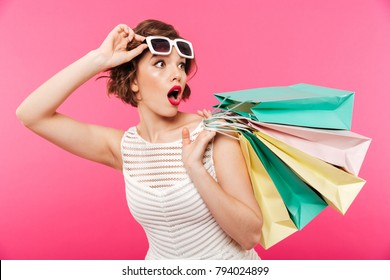 Portrait of a shocked girl dressed in dress holding shopping bags and looking away isolated over pink background