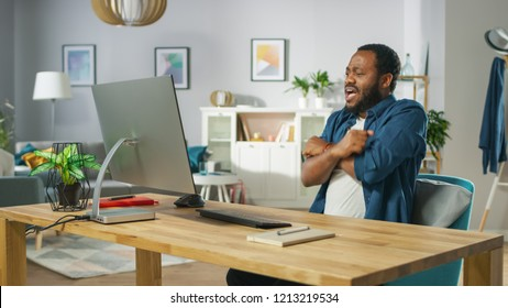 Portrait of the Shocked Handsome African American Man Sitting at His Workplace. Young Man Watching Screamers at Home.
