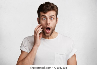Portrait of shocked handsome blue eyed man keeps mouth widely opened, being in stupor as watches news online, wears white casual t shirt, isolated over concrete wall. Shock and surprisment concept