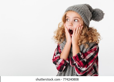 Portrait of a shocked little girl dressed in winter hat and scarf looking away at copy space isolated over white background