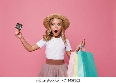 Portrait of a shocked little girl in hat and skirt holding shopping bags and a credit card while standing and looking at camera isolated over pink background