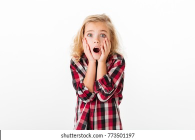 Portrait of a shocked little girl holding hands at her face and looking at camera isolated over white background