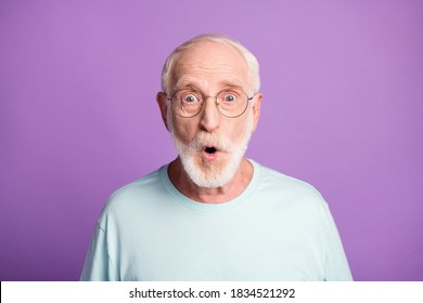 Portrait of shocked old man wear casual cloth eyeglasses open mouth isolated on purple color background