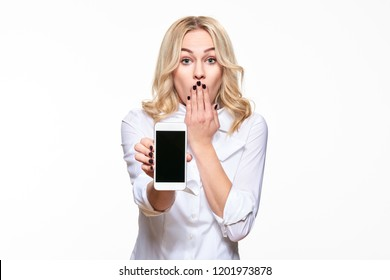 Portrait of shocked pretty blond business woman with hand on her mouth showing mobile phone blank screen isolated over white background. Shock, disbelief, anxiety, secret, panic, gossip.