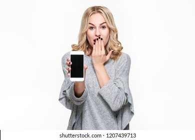 Portrait of shocked pretty blond woman with hand on her mouth showing mobile phone blank screen isolated over white background. Shock, disbelief, anxiety, secret, panic, gossip.