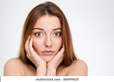 Portrait of shocked pretty young woman touching her face over white background