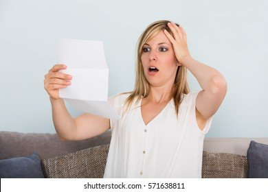 Portrait Of A Shocked Sad Young Woman Reading Letter