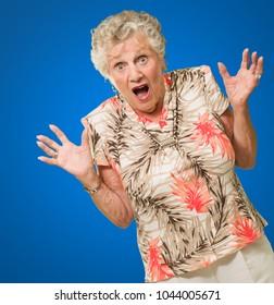 Portrait Of Shocked Senior Woman On Blue Background