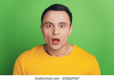 Portrait of shocked speechless guy open mouth stunned face on green background