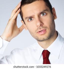 Portrait of shocked thinking businessman, against grey background