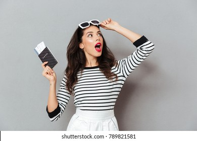 Portrait of a shocked woman holding passport with flying tickets and looking away isolated over gray background