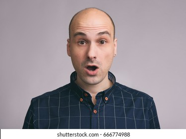 Portrait of shocked young bald man with open mouth