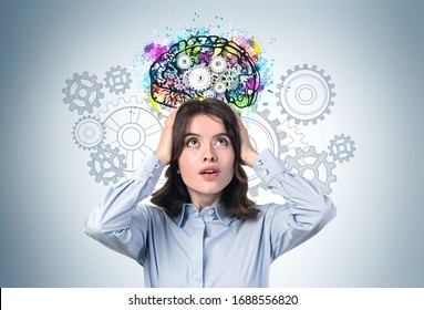 Portrait of shocked young businesswoman or student with long wavy hair standing near grey wall with colorful brain sketch drawn on it. Concept of education and brainstorming