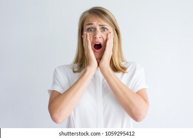 Portrait of shocked young Caucasian woman wearing white shirt holding head in hands and looking at camera. Fear and surprise concept