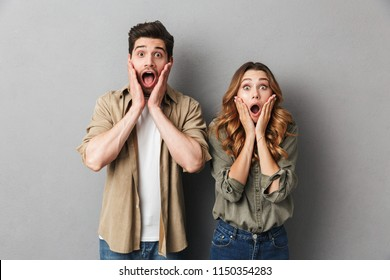Portrait of a shocked young couple standing together isolated over gray background,looking at camera