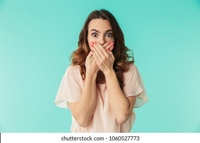 Portrait of a shocked young girl in dress looking at camera with mouth covered isolated over blue background