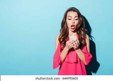 Portrait if a shocked young girl in dress looking at mobile phone isolated over blue background