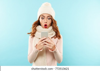 Portrait of a shocked young girl dressed in hat and scarf looking at mobile phone isolated over blue background