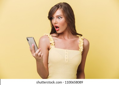 Portrait of a shocked young girl looking at mobile phone isolated over yellow background