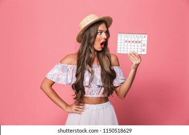 Portrait of a shocked young girl in summer clothes showing periods calendar over pink background
